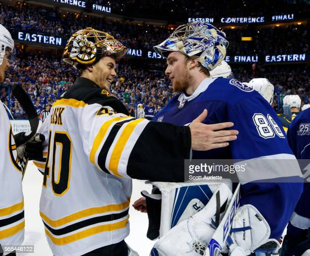 Goalie Andrei Vasilevskiy of the Tampa Bay Lightning celebrates the series win and shakes hands with Tuukka Rask of the Boston Bruins during Game...