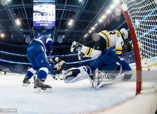Goalie Andrei Vasilevskiy of the Tampa Bay Lightning gets knocked over by Brad Marchand of the Boston Bruins during the first period at Amalie Arena...