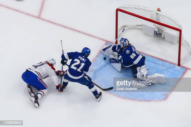 Goalie Andrei Vasilevskiy of the Tampa Bay Lightning makes a save as teammate Brayden Point and Eric Staal of the Montreal Canadiens look for the...