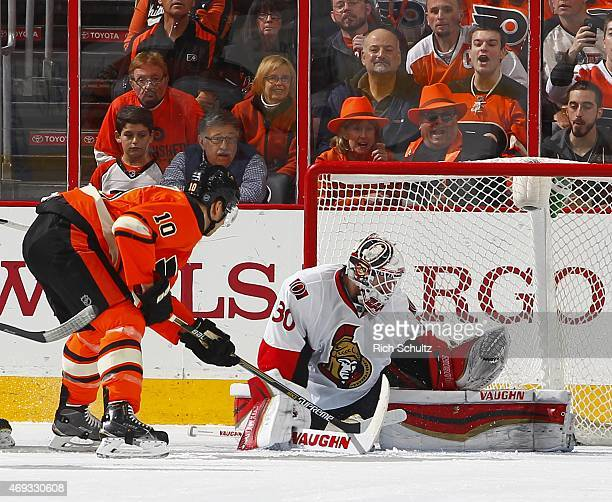 Goalie Andrew Hammond of the Ottawa Senators makes a save as Brayden Schenn of the Philadelphia Flyers looks for a rebound during first period at...