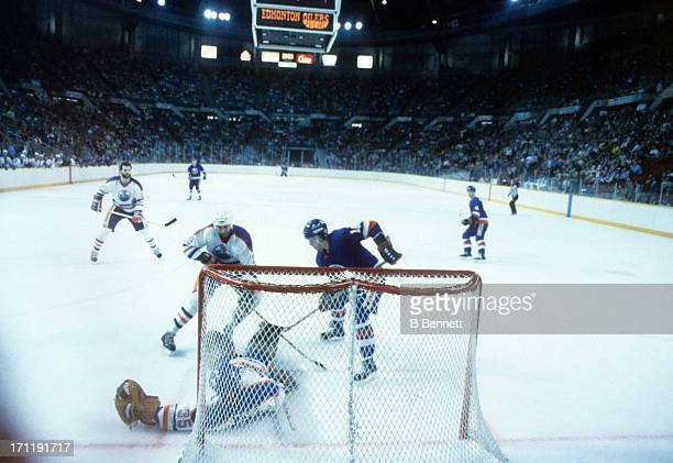 Goalie Andy Moog and Don Jackson of the Edmonton Oilers defend the net as Pat LaFontaine of the New York Islanders looks for the rebound during the...