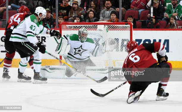 Goalie Anton Khudobin of the Dallas Stars positions himself for a save as the shot of Jakob Chychrun of the Arizona Coyotes hits the crossbar during...