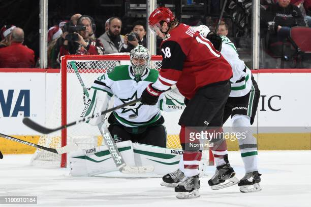 Goalie Anton Khudobin of the Dallas Stars watches the puck as Christian Dvorak of the Arizona Coyotes and Esa Lindell of the Stars battle for the...
