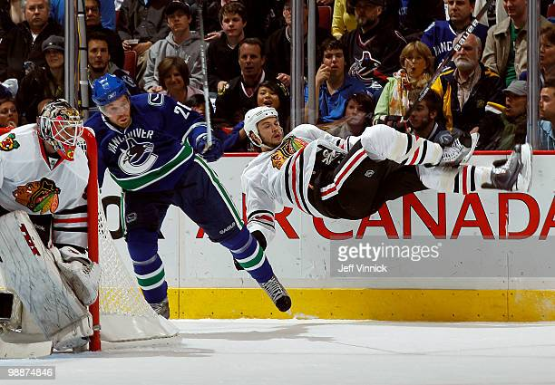 Goalie Antti Niemi of the Chicago Blackhawks looks on as Mikael Samuelsson of the Vancouver Canucks checks Brent Seabrook of the Chicago Blackhawks...