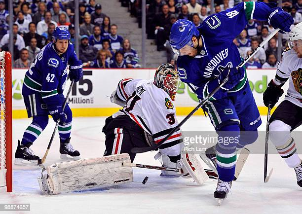Goalie Antti Niemi of the Chicago Blackhawks stops the backhand shot of Steve Bernier of the Vancouver Canucks as Kyle Wellwood of the Canucks looks...