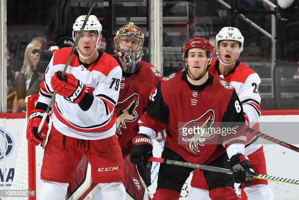 Goalie Antti Raanta and Jordan Oesterle of the Arizona Coyotes look for the puck while defending Micheal Ferland and Sebastian Aho of the Carolina...