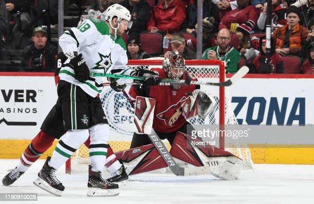Goalie Antti Raanta of the Arizona Coyotes attempts to make a save on the re-direction attempt by Jason Dickinson of the Dallas Stars during the...