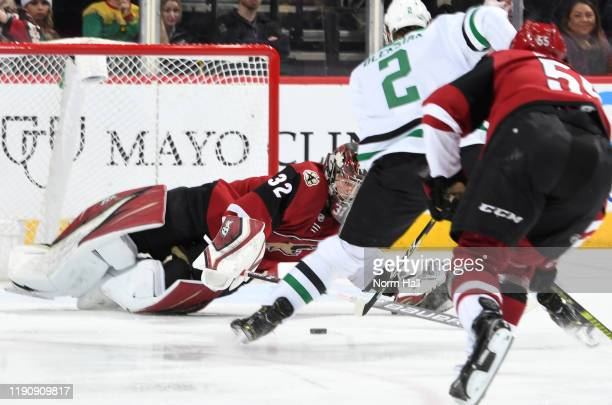 Goalie Antti Raanta of the Arizona Coyotes dives to cover the puck as Jamie Oleksiak of the Dallas Stars skates in on goal during the second period...
