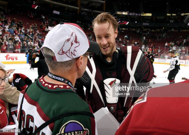 Goalie Antti Raanta of the Arizona Coyotes gives a fan his jersey as part of the Fan Appreciation Night Jerseys off their Back event following the...