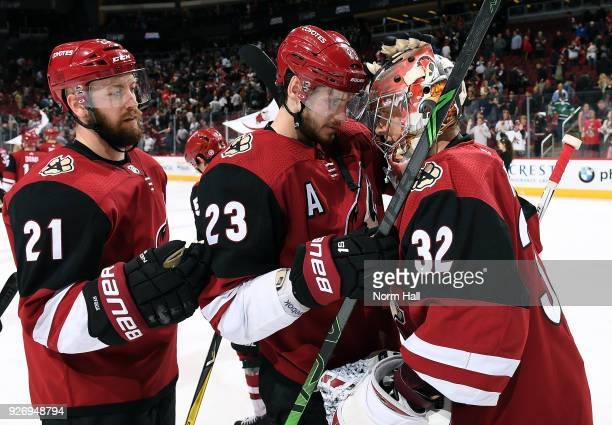 Goalie Antti Raanta of the Arizona Coyotes is congratulated by teammates Oliver EkmanLarsson and Derek Stepan following a 21 victory against the...