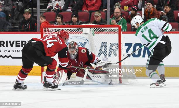Goalie Antti Raanta of the Arizona Coyotes looks to cover the puck after making a save on the shot by Jamie Benn of the Dallas Stars as Carl...