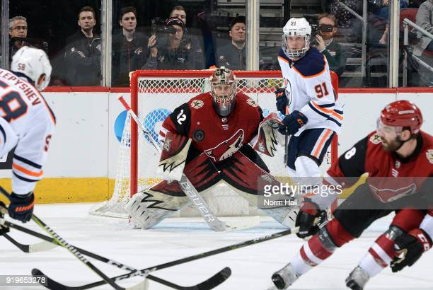 Goalie Antti Raanta of the Arizona Coyotes looks to make a save on the shot by Anton Slepyshev of the Edmonton Oilers as Drake Caggiula of the Oilers...
