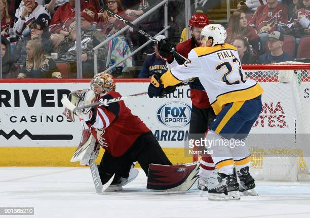 Goalie Antti Raanta of the Arizona Coyotes makes a glove save as Kevin Fiala of the Nashville Predators tries to deflect the puck and Jason Demers of...