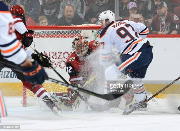 Goalie Antti Raanta of the Arizona Coyotes makes a save as Connor McDavid of the Edmonton Oilers skates in during the first period at Gila River...