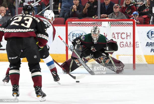 Goalie Antti Raanta of the Arizona Coyotes positions himself for a save as JT Compher of the Colorado Avalanche skates in with the puck during the...
