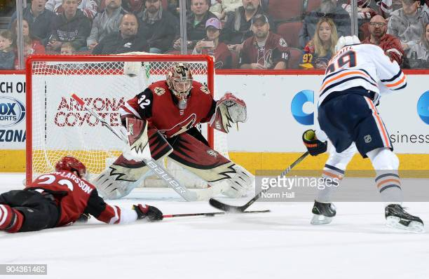 Goalie Antti Raanta of the Arizona Coyotes positions himself for a save as Leon Draisaitl of the Edmonton Oilers skates in with the puck and Oliver...