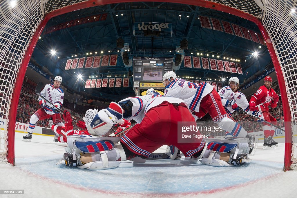 Goalie Antti Raanta #32 of the New York Rangers makes a save as players crash the front of the net during an NHL game against the Detroit Red Wings at Joe Louis Arena on March 12, 2017 in Detroit, Michigan. The Rangers defeated the Wings 4-1.