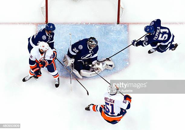 Goalie Ben Bishop of the Tampa Bay Lightning makes a save while teammates Matt Carle and Valtteri Filppula look for the rebound against Josh Bailey...