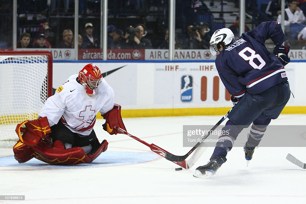 Goalie Benjamin Conz #1 of Switzerland stops forward Brock Nelson #8 of USA during the 2011 IIHF World U20 Championship game between USA and Switzerland on December 31, 2010 at HSBC Arena in Buffalo, New York.