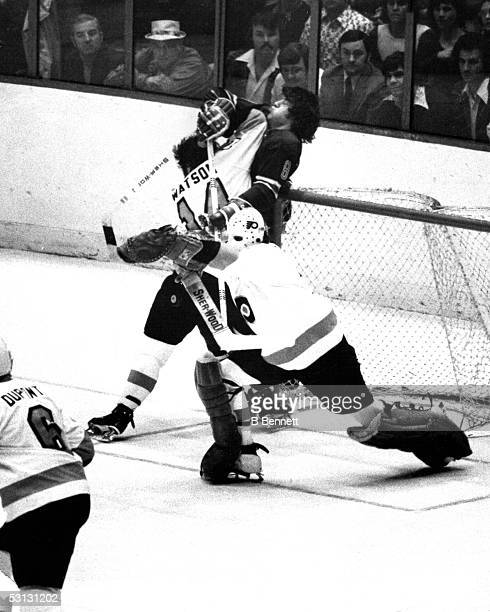Goalie Bernie Parent of the Philadelphia Flyers deflects a shot off of teammate Joe Watson as he elbows Steve Vickers of the New York Rangers during...