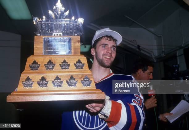 Goalie Bill Ranford of the Edmonton Oilers celebrates with the Conn Smythe Trophy after Game 5 of the 1990 Stanley Cup Finals against the Boston...