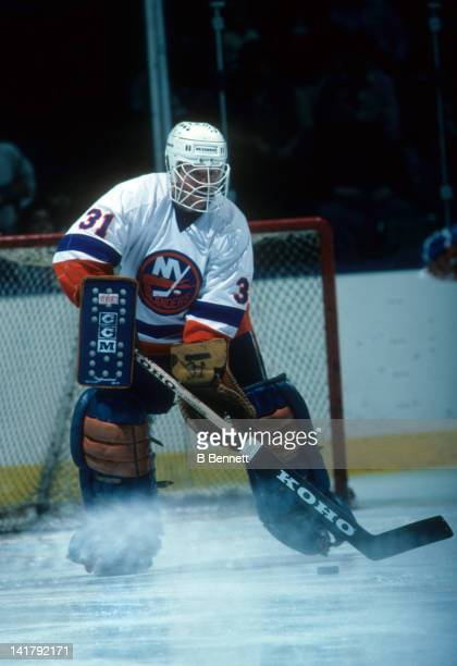 Goalie Billy Smith of the New York Islanders looks to move the puck during an NHL game circa 1986 at the Nassau Coliseum in Uniondale New York