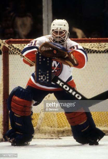 Goalie Billy Smith of the New York Islanders makes the glove save during an NHL game circa 1985 at the Nassau Coliseum in Uniondale New York