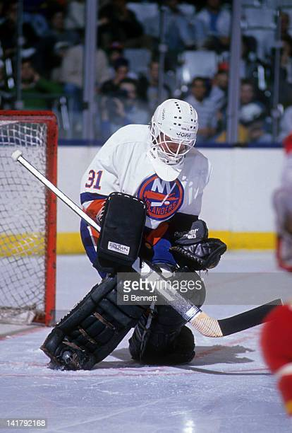 Goalie Billy Smith of the New York Islanders makes the save during an NHL game against the Calgary Flames circa 1987 at the Nassau Coliseum in...