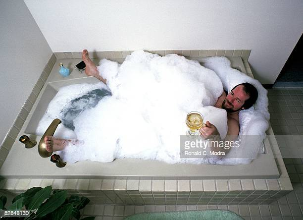 Goalie Billy Smith of the New York Islanders relaxes in the bathtub at home in January 1982 in Long Island New York