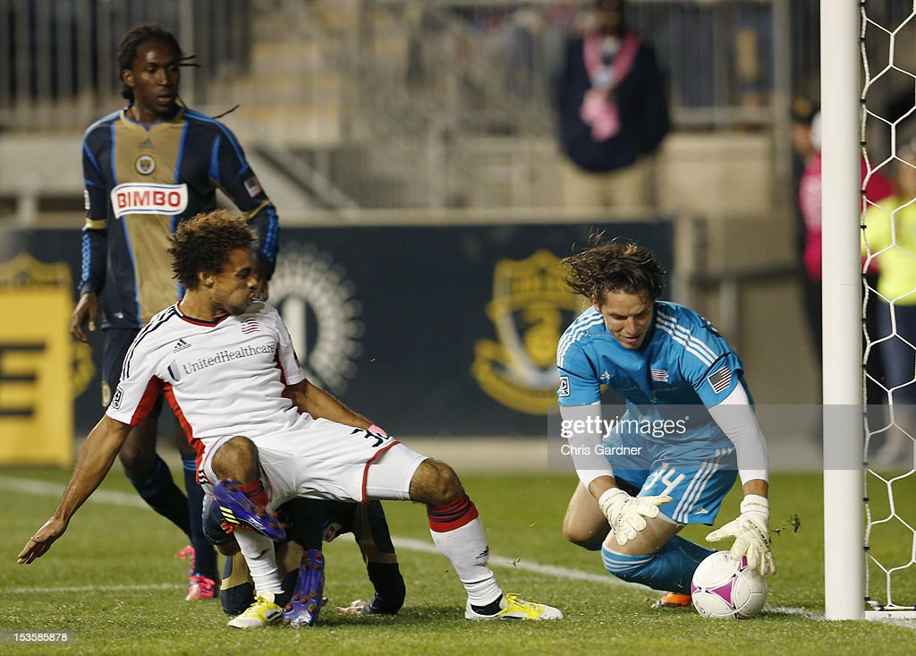 Goalie Bobby Shuttleworth #34 of the New England Revolution falls on a shot by Keon Daniel #26 of the Philadelphia Union as Kevin Alston #30 of the New England Revolution covers at PPL Park on October 6, 2012 in Chester, Pennsylvania.