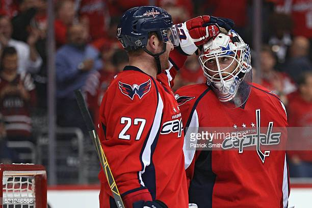 Goalie Braden Holtby of the Washington Capitals celebrates with teammate Karl Alzner after defeating the Philadelphia Flyers in Game One of the...