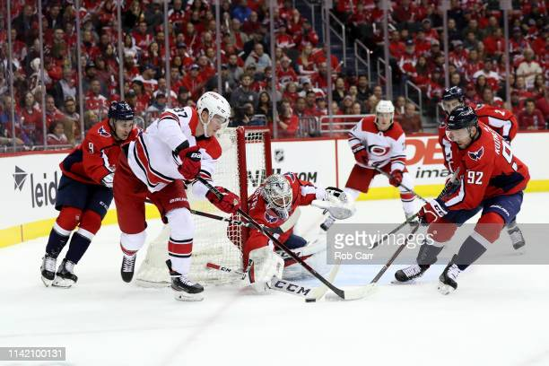 Goalie Braden Holtby of the Washington Capitals deflects a shot by Andrei Svechnikov of the Carolina Hurricanes in the first period in Game One of...