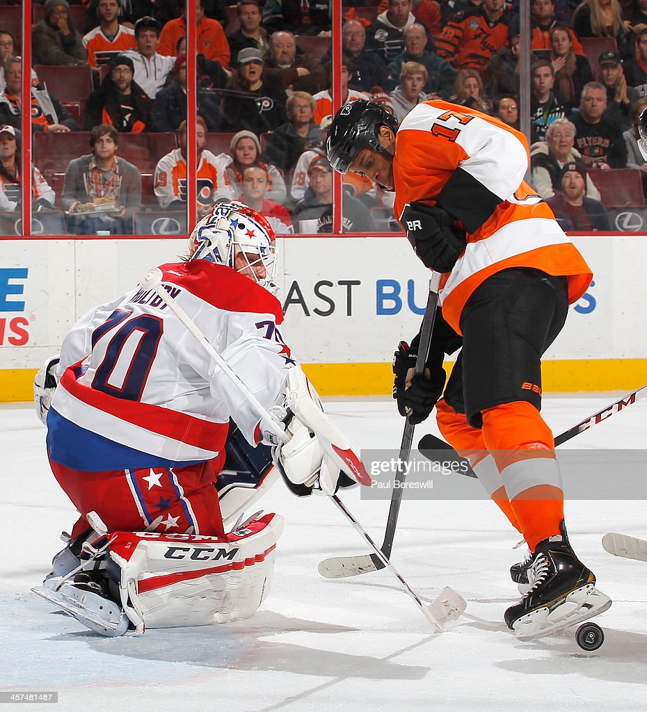 Goalie Braden Holtby #70 of the Washington Capitals knocks the puck back past Wayne Simmonds #17 of the Philadelphia Flyers for a save in the second period of an NHL hockey game at Wells Fargo Center on December 17, 2013 in Philadelphia, Pennsylvania.