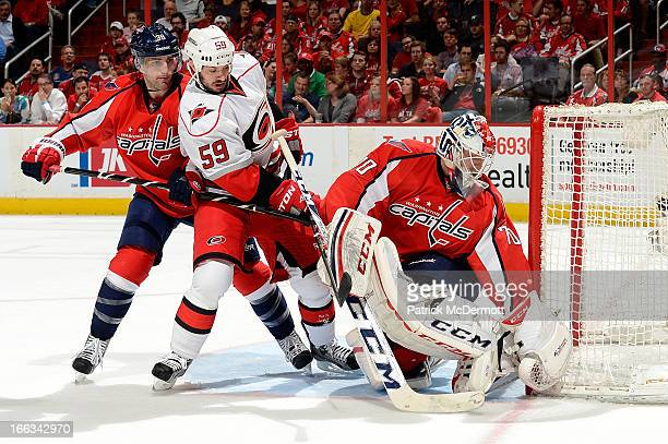 Goalie Braden Holtby of the Washington Capitals smothers the shot from Chad LaRose of the Carolina Hurricanes during the second period of an NHL game...