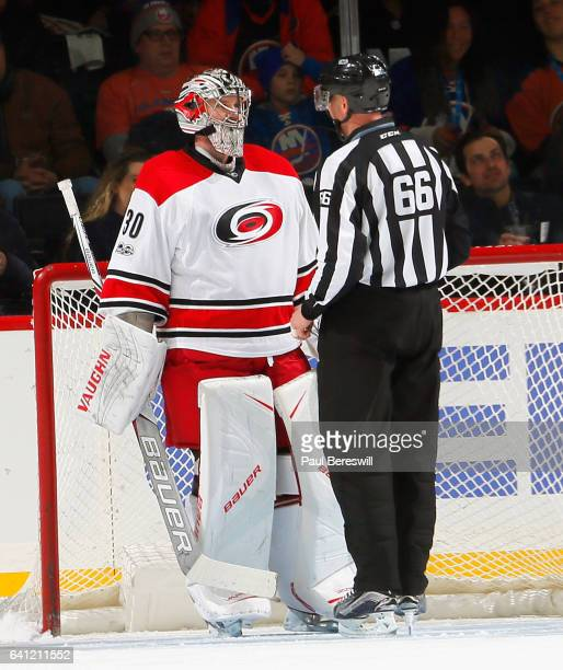 Goalie Cam Ward of the Carolina Hurricanes talks with linesman Darren Gibbs during a break in the action in an NHL hockey game against the New York...