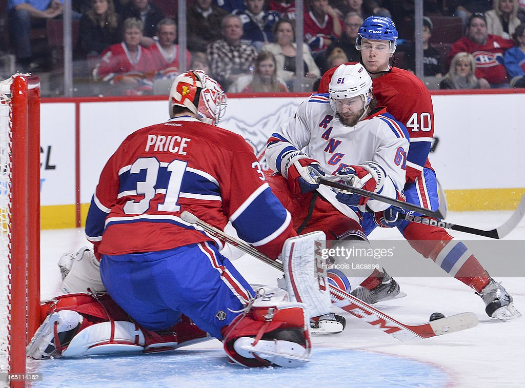 Goalie Carey Price #31 of the Montreal Canadiens makes a save as teammate Nathan Beaulieu #40 ties up Rick Nash #61 of the New York Rangers during the NHL game on March 30, 2013 at the Bell Centre in Montreal, Quebec, Canada.