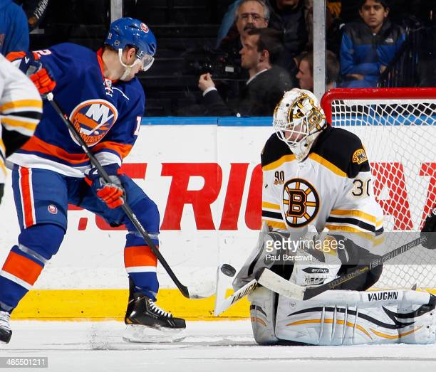 Goalie Chad Johnson of the Boston Bruins stops a shot by Josh Bailey of the New York Islanders during the first period of an NHL hockey game at...