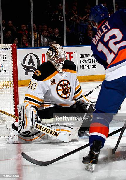 Goalie Chad Johnson of the Boston Bruins stops a shot by Josh Bailey of the New York Islanders in the second period of an NHL hockey game at Nassau...