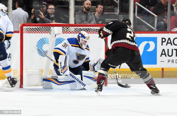 Goalie Chad Johnson of the St Louis Blues looks to make a save as Derek Stepan of the Arizona Coyotes skates in with the puck during the first period...