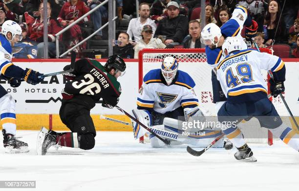 Goalie Chad Johnson of the St Louis Blues tries to stop the shot of Christian Fischer of the Arizona Coyotes as Robert Bortuzzo and Ivan Barbashev of...