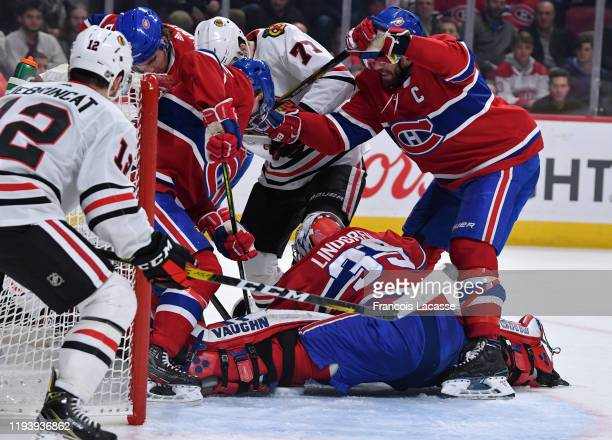Goalie Charlie Lindgren of the Montreal Canadiens covers up the puck with help from teammate Shea Weber and under pressure from Kirby Dach of the...