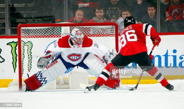 Goalie Charlie Lindgren of the Montreal Canadiens stops this scoring attempt by Jack Hughes of the New Jersey Devils during the shootout of an NHL...