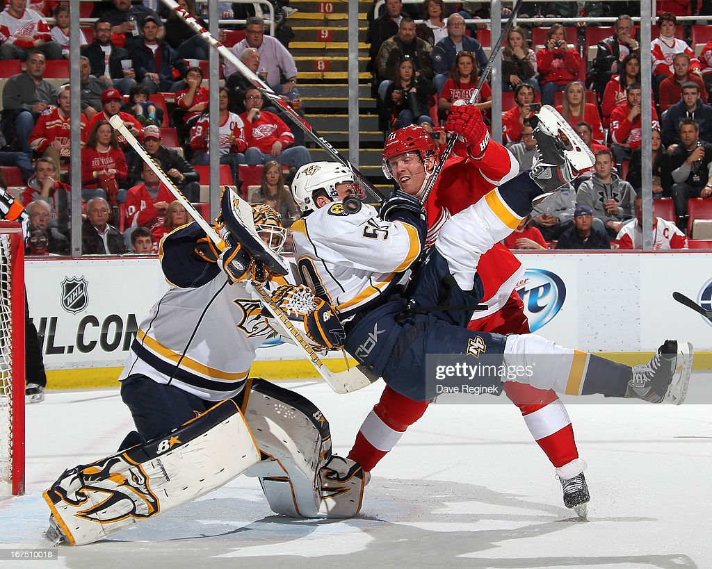 Goalie Chris Mason #30 of the Nashville Predators tries to locate the puck as teamate Roman Josi #59 gets taken out by Daniel Cleary #11 of the Detroit Red Wings during a NHL game at Joe Louis Arena on April 25, 2013 in Detroit, Michigan.