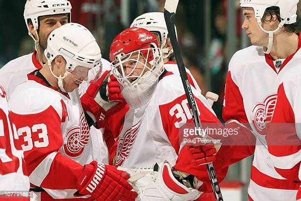 Goalie Chris Osgood of the Detroit Red Wings is congratulated by Kris Draper and his teammates after he earned his 400th win with a victory over the...