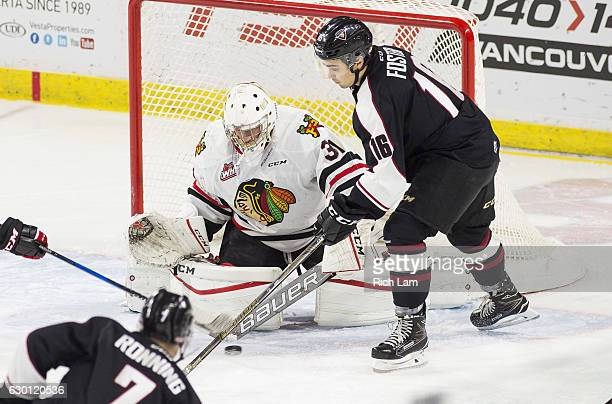 Goalie Cole Kehler of the Portland Winterhawks stops the shot of Ty Ronning of the Vancouver Giants while Thomas Foster looks for a rebound during...