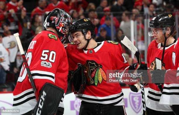 Goalie Corey Crawford and Alex DeBrincat of the Chicago Blackhawks celebrate after defeating the Anaheim Ducks 73 at the United Center on November 27...