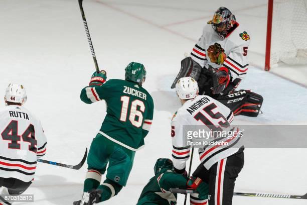 Goalie Corey Crawford makes a save while his Chicago Blackhawks teammates Jan Rutta and Artem Anisimov defend against Jason Zucker of the Minnesota...