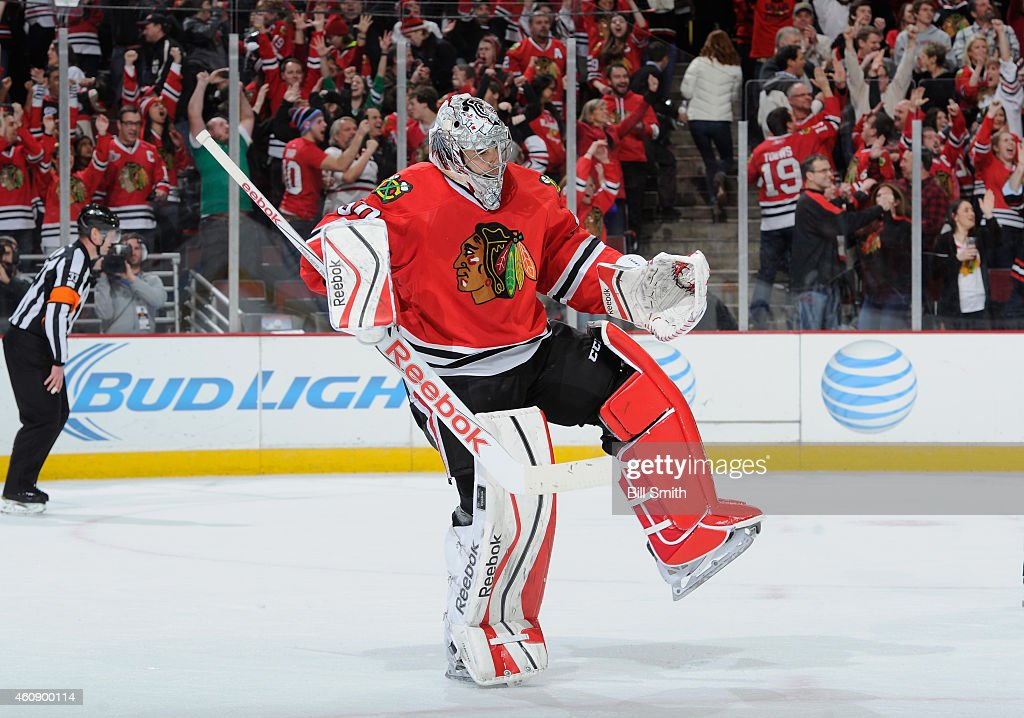 Goalie Corey Crawford #50 of the Chicago Blackhawks celebrates after defeating the Nashville Predators 5-4 during the NHL game at the United Center on December 29, 2014 in Chicago, Illinois.