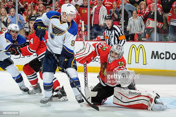 Goalie Corey Crawford of the Chicago Blackhawks grabs the puck next to Jaden Schwartz of the St Louis Blues as Alexander Steen of the Blues and...