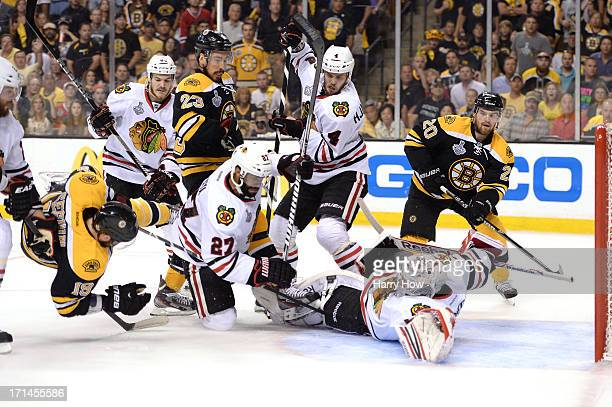 Goalie Corey Crawford of the Chicago Blackhawks reaches to make a save as Tyler Seguin of the Boston Bruins is up ended in front of the net in the...